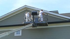 Two professional house painters painting a townhouse in a residential area.