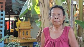 A proud Thai lady stands outside her quaint Thai home in the slums of Bangkok, Thailand.