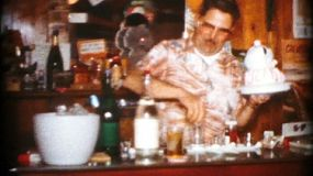 A proud bartender shows off his drink making skills for friends and family at his new bar in 1964.