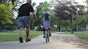 An excited dad helps her young Asian daughter ride her pink bike without training wheels for the first time.