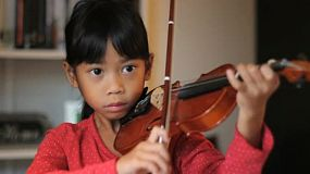 A pretty 6 year-old Asian girl proudly  finishes practicing her violin in the living room.