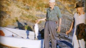 A proud old man catches a fish and then shares it with family and friends as a picnic lunch down by the sea in 1966.