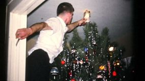 A handsome teenage boy puts the pretty angel on top of the tree at Christmas in 1961.