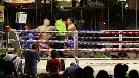 A fighter delivers a quick series of strikes in a Muay Thai kick boxing fight in Bangkok, Thailand.