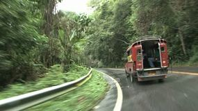 A red pick up truck drives on a switch back mountain road in Chiang Mai, Thailand.