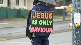 A very committed religious follower of Jesus, stands on a busy street corner wearing a sign that proclaims that Jesus is the only Saviour!