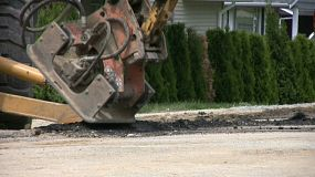 A close up shot of a road compactor machine working on flattening some freshly laid asphalt on a suburban street. (HD 1080p30)