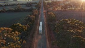 A road train truck travelling down a country road in Western Australia as the light from the sunset encroaches the frame.