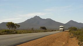 A road train driving down a highway in outback Australia, with the Stirling Ranges in the background.