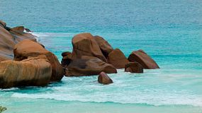 Rocks near a cape and a beach, in the clear blue ocean waters in Western Australia.