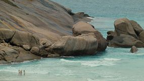 Young women enjoying the beautiful waters of Esperance, Western Australia, near a rocky cape.