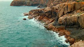 Dangerous rocks and cliffs, with a man fishing on the rocky coastline in Western Australia.