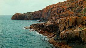 Cliff faces along the coastline in South West Western Australia, with a man standing on the rocks and fishing.
