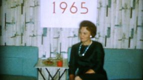 A lady sits under a sign that says 1965 and waits for the New Year's Eve party to start at the end of 1964.