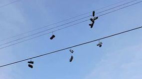 A whole bunch of running shoes hanging on some telephone wires in the city.