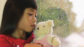 A sad seven year old Asian girl sits by a window watching the rain fall while being comforted by her Teddy Bear.