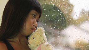 A sad seven year old Asian girl kisses her Teddy Bear as she sits by the window watching the rain fall.