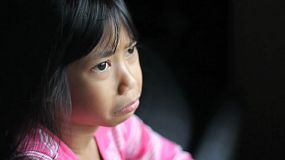 A sad little 8 year old Asian girl stares out the window.