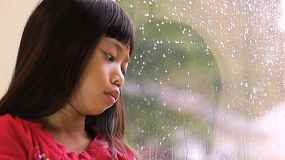 A sad little seven year old Asian girl sits by the window watching the rain drops fall.