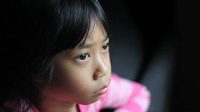 A sad lonely 8 year old Asian girl looks towards the camera after staring out the window.