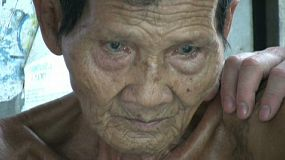A close up shot of a sad old Thai man holding back the tears in the slums of Bangkok.