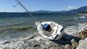An abandoned shipwrecked sailboat rests on the rocky shore of English Bay in Vancouver, BC.