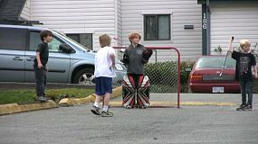 A young boy scores a goal while playing road hockey with his friends.