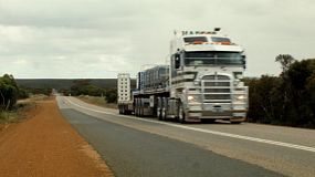 A big semi trailer truck driving down a highway in country Australia.