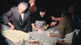 Office management careful cuts a big slab cake and serves it to the staff at the year end company Christmas party in 1962.