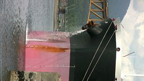A close up, vertical shot of a large container ship purging water while it sits in port at Vancouver, BC. (HD 1080p30)