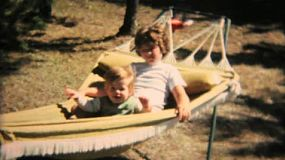 Loving sisters enjoy spending time together swinging on the hammock in the summer of 1968.