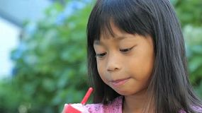 A cute little 6 year old Thai girl enjoys finishing her popsicle on a hot summer's day.