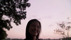 A happy Asian woman, enjoying time in nature at dusk.