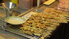 A Thai street food stall with skewers of grilled squid laid out ready for purchase in Bangkok.