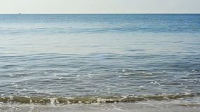 Still ocean, with small waves lapping at the shore, in Rayong, Thailand.