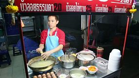Thai man cooking Thai dumplings at his street stall, ready to sell this Thai desert, often served with coconut cream, in Bangkok, Thailand.
