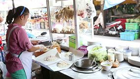 "A street vendor chops up chicken and puts in on rice as she prepares takeaway meals of ""Khao Man Gai"" in Bangkok, Thailand."