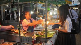BANGKOK, THAILAND - NOVEMBER 2013: A woman selling grilled pork on a stick to a female customer, at her street stall in Bangkok, Thailand.