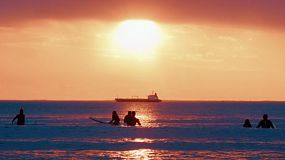 Silhouettes of surfers at South Cottesloe Beach in Western Australia, as the sun sets in the background, with a ship on the horizon.