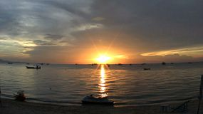 A lovely shot of a sunset on Pattaya Bay, Thailand with a variety of boats and jet skis in the foreground.