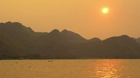 View of the sun setting behind mountains from across the Mae Klong River in Kanchanaburi, Thailand, on a hazy day. There is a person on a kayak paddling on the river, in the distance.