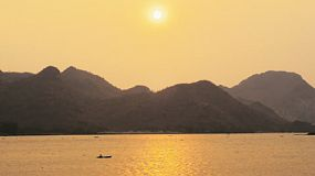 Beautiful view of the sun setting behind mountains from across the Mae Klong River in Kanchanaburi, Thailand, on a hazy day. There is a person on a kayak floating on the river, in the distance.