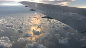 Clouds float above the ocean as the sun sets over the Pacific Ocean during an overseas flight.