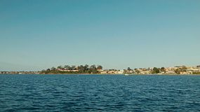 Looking along the Swan River, with many houses with scenic views of the river, in Perth, Australia.