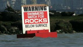"A ""Warning - Swimmers Watch For Rocks Below Surface"" sign at the beach."