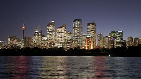Night time lapse of the Sydney City skyline in the fading light of dusk, with the city lights reflecting off the water.