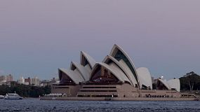Ferries passing the Sydney Opera House at dusk.