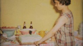 A pretty teenage girl cuts her birthday cake at her birthday party.