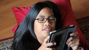 A cute Asian teenager enjoys spending time playing a game on her new digital tablet in the living room.