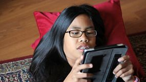A cute Asian teenager with braces enjoys spending time playing a game on her new digital tablet in the living room.